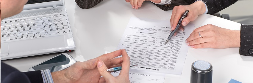 Three people sitting at a table signing documents, hands close-up